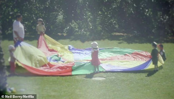 Madeleine McCann (centre, in pink dress) holds on to a 'play parachute' with four other children at the Portuguese resort where her family was staying in 2007