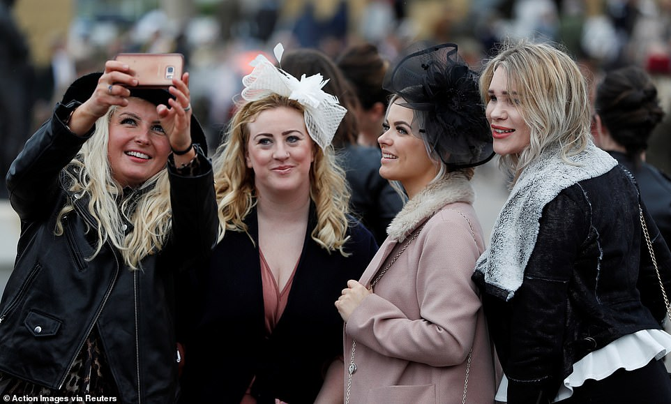 A gang of female revellers pose for a snap as they prepare for the first race of the day to get underway