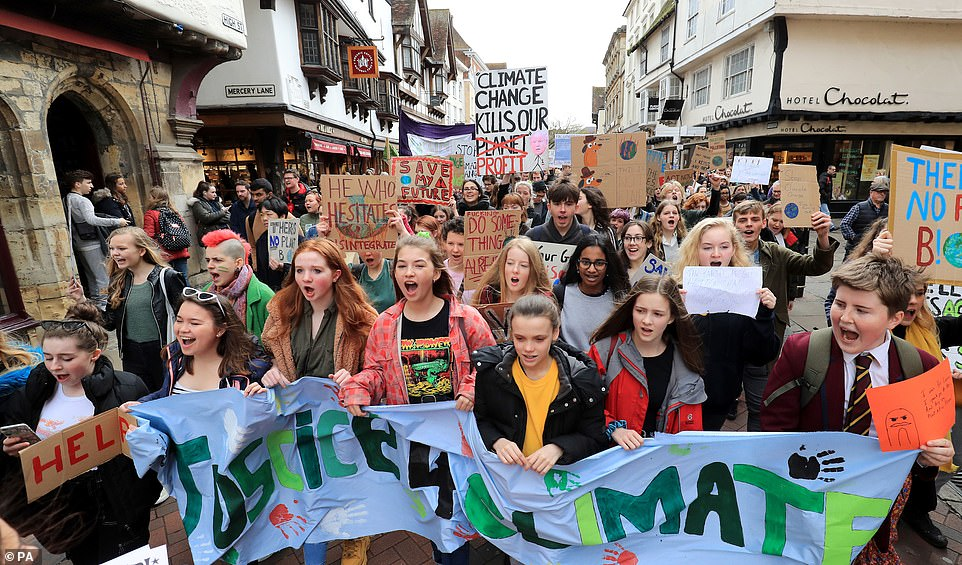 Students take part in a global school strike for climate change in Canterbury, Kent. One boy in school uniform appears to have walked straight out of school