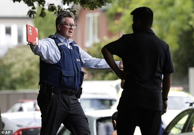A police officer gestures to a person outside the mosque after the shooting in Christchurch