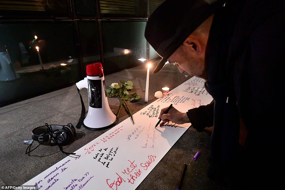 A man in Brussels leans down and pens a tribute to the victims at the site near the New Zealander Embassy, where white roses had also been left