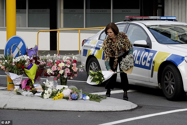 A woman places flowers at a make-shift memorial near the mosque in Christchurch