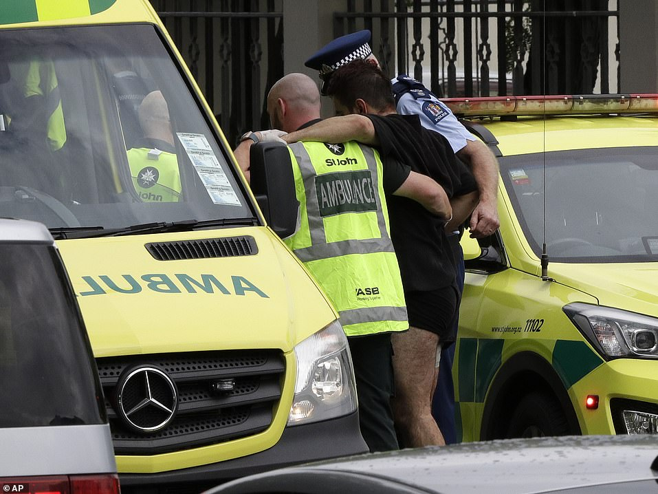 At least one gunman opened fire at a mosque in New Zealand , shooting at worshippers and killing dozens of people. Pictured: A wounded man is helped from the scene