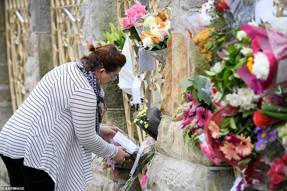 A woman places flowers outside the Lakemba Mosque in south-west Sydney on Saturday following the mass-shooting in Christchurch on Friday