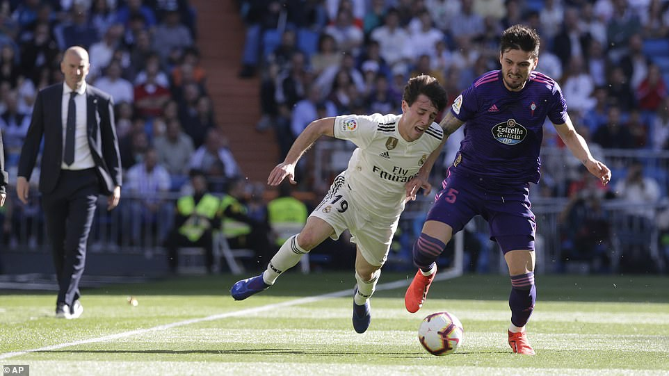 Zidane watches on from the sidelines asOdriozola (left) challenges with Celta's Yokuslu for the ball during the first half