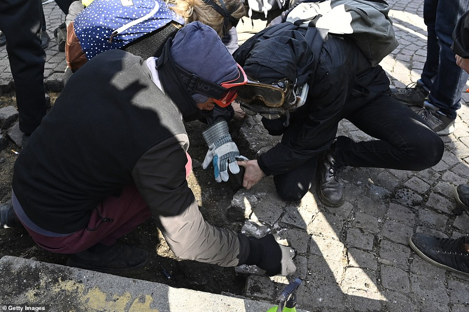 Yellow vests protesters break the rocks on sidewalks during the demonstrations