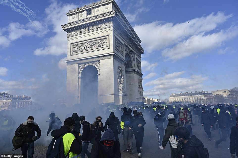 Security forces intervene yellow vest protesters with tear gas during a demonstration on avenue Champs Elysees in Paris