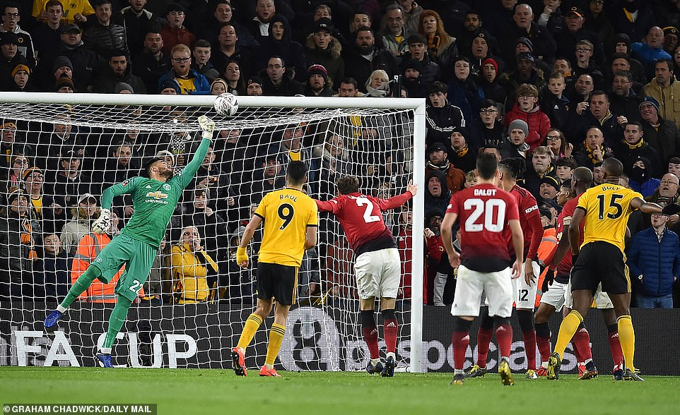 Manchester United goalkeeper Sergio Romero makes a save to deny Jimenez from finding the net with a header