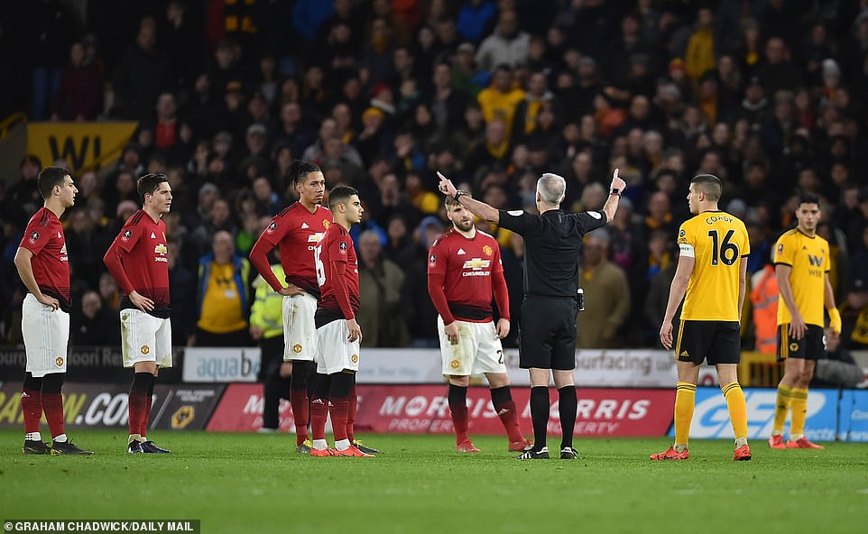 Referee Martin Atkinson indicates that the red card has been overturned by VAR and Lindelof received a yellow card instead