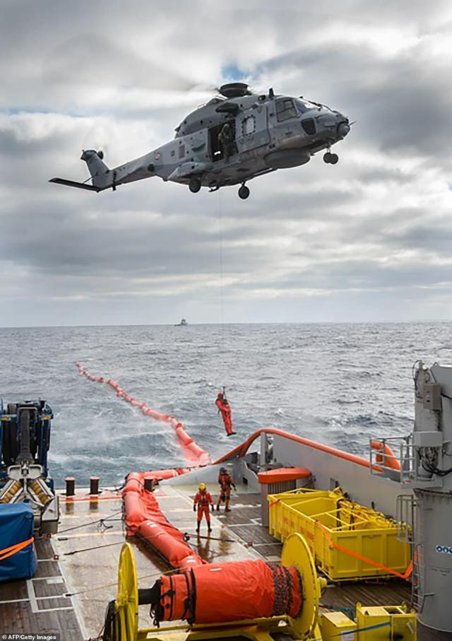 The French Navy released this image from Saturday showing a military helicopter flying over the oil spill