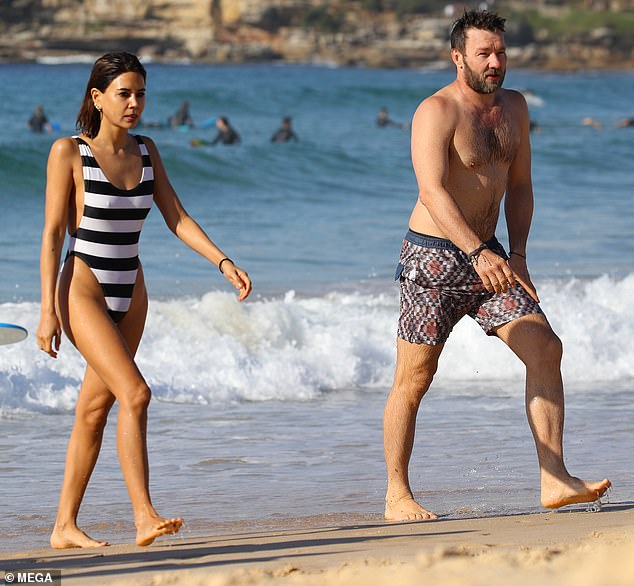 Hot couple alert! Stripping down to skimpy swimwear, the genetically-blessed duo were hard to miss as they frolicked in the autumnal surf