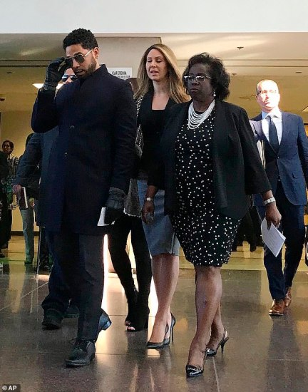 Smollett walks past a bank of photographers, adjusting his sunglasses, before leaving the court with his laeyers