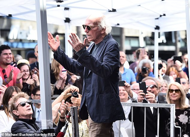 Making a scene: At one point he threw his hands up as fans took photos of him