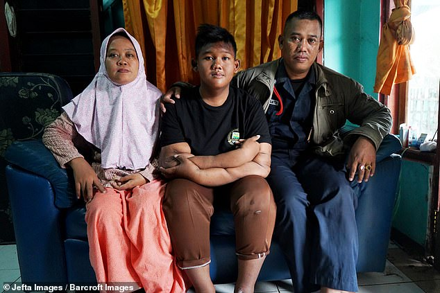 Now a healthier size, Arya is pictured with his parents at their home in West Java, Indonesia, last month. The pair admit they 'spoilt' their son and let him eat whatever he wanted