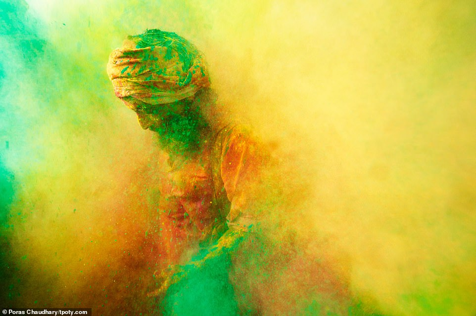 A man wearing a turban emerges from a cloud of colours during the festival of Holi in the sacred city of Mathura in Uttar Pradesh, northern India