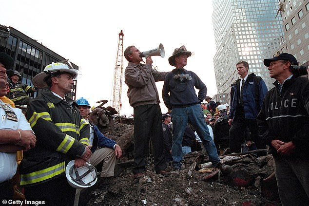 Standing atop rubble, President George W. Bush rallies firefighters and rescue workers during an impromptu speech at the site of the collapsed World Trade Center in New York City on September 14, 2001