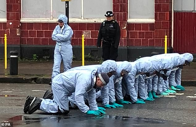 Forensics are pictured at the scene in Manor Park, east London, where a man in is 20s was killed in a gun and knife attack on Monday