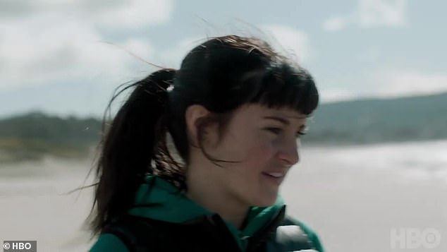 Huh?Shailene's face is seen as she walks by the shore. She asks the man what that means