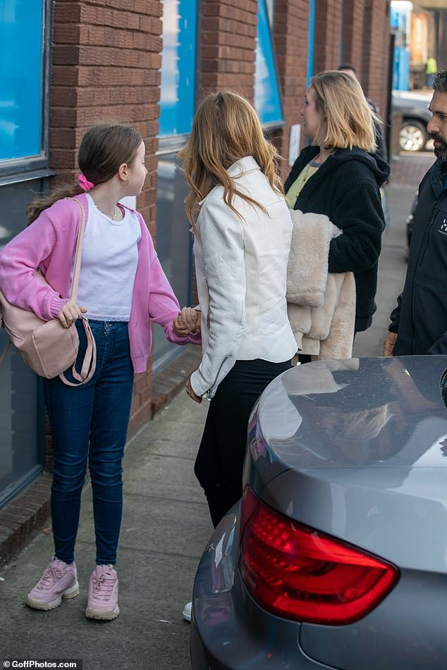 Stylish: Geri wore a white leather jacket with black trousers while her daughter was dressed in pink