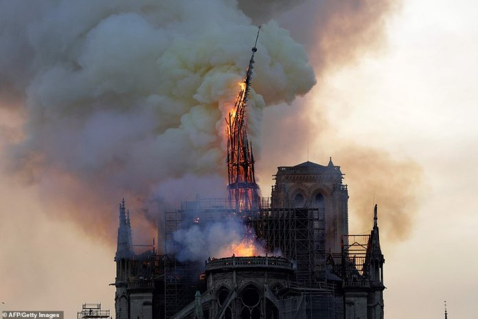 The famous spire of Notre Dame collapsed dramatically at around 7.15pm GMT after the blaze tore through the wooden structure at the top of the building