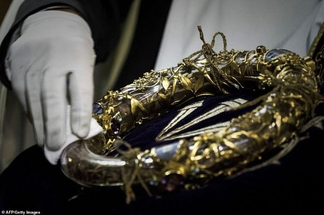 A priest pictured wiping the Crown of Thorns, a relic of the passion of Christ, protected in a case and kept atNotre Dame Cathedral in Paris