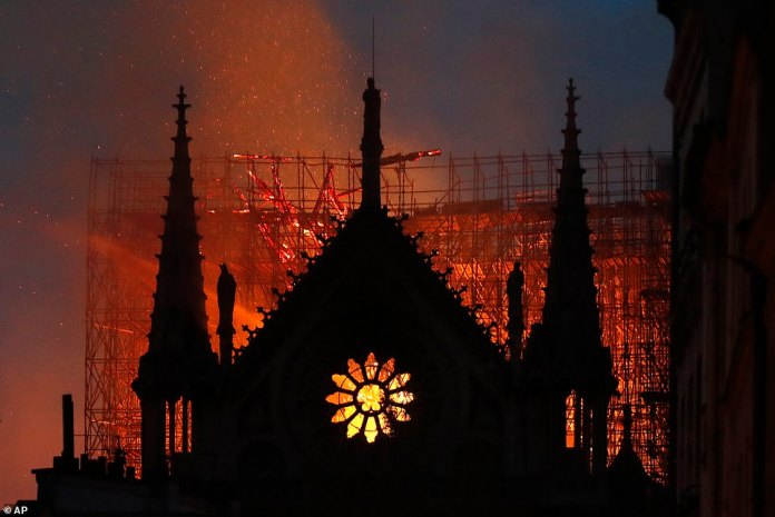 The burning orange of the flames can be seen through the rose petal window this evening as Parisians and tourists look on in horror as the blaze continues to spread at the cathedral