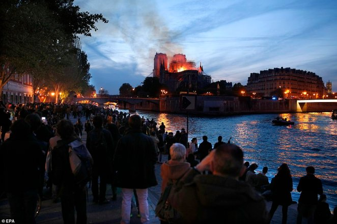 Parisians gather on the River Seine this evening to look at the flames spreading throughout the cathedral. The blaze started in the late afternoon