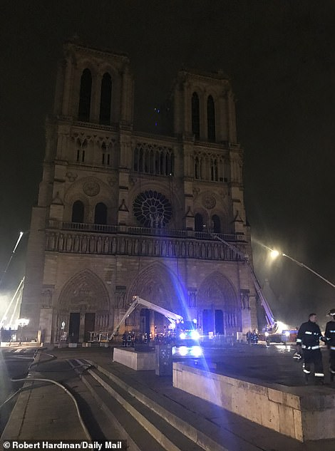 Outside Notre Dame where cranes and firemen were still hard at work