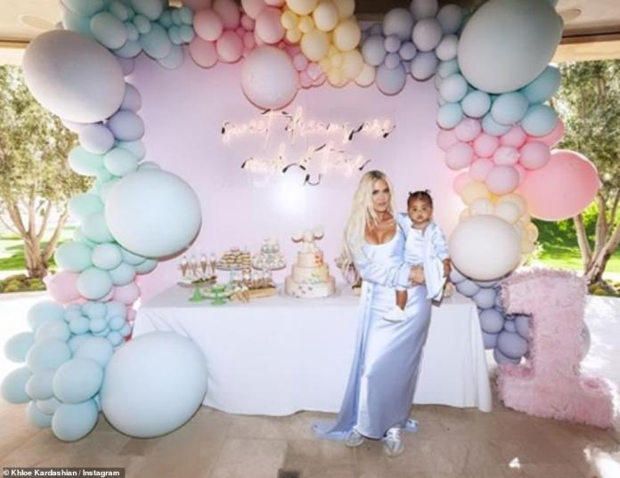 Rainbow: Khloe clung to her child as they posed in front of a balloon appearance with unicorn motifs surrounding a table full of cakes
