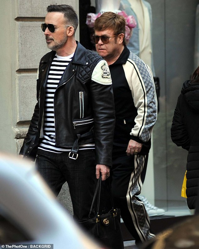 Fabulous fun: Elton John enjoyed a shopping spree with his husband David Furnish as they hit the streets in Milan, in Italy on Tuesday