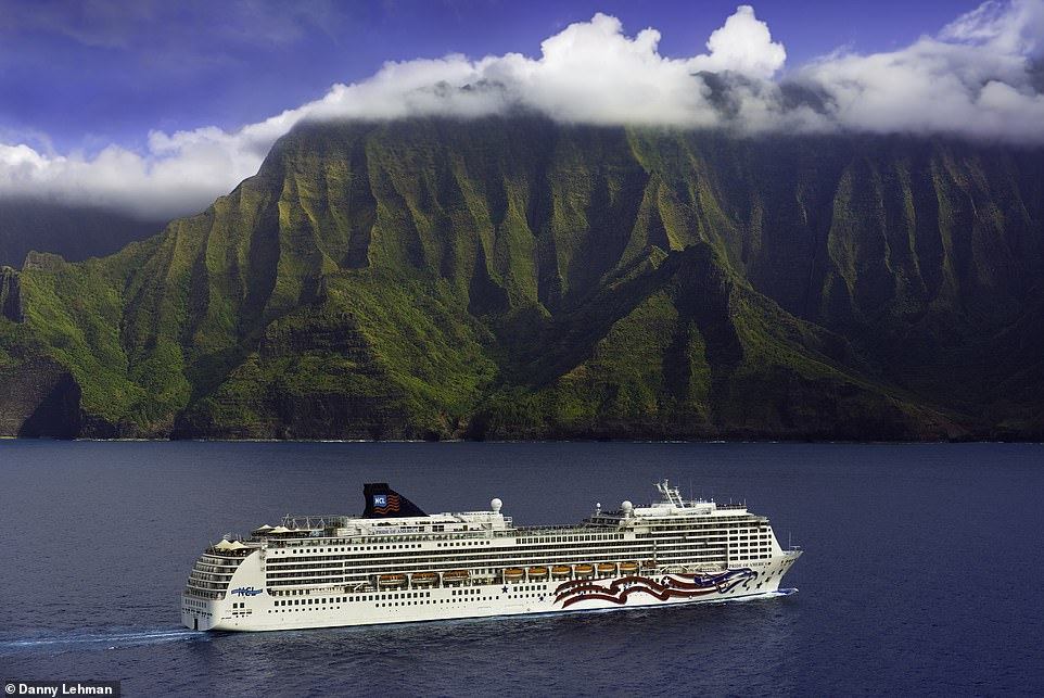 The dramatic Na Pali Coast of Kauai in Hawaii with the cliff towering above Norwegian Cruise Line's boat, Pride of America. This is where much of the filming took place for Steven Spielberg's 1993 blockbuster, Jurassic Park. The Pride of America sails around Hawaii all-year-round and highlights on the agenda includewhale watching and witnessing the Kilauea Volcano