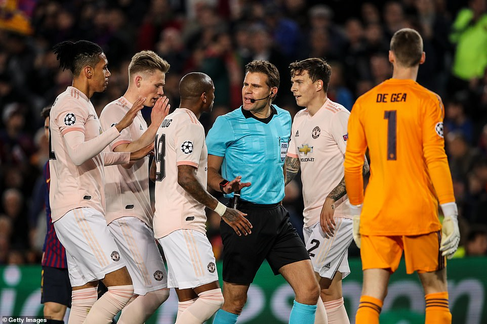 United players surround the German referee after he awarded Barcelona a penalty during the first half