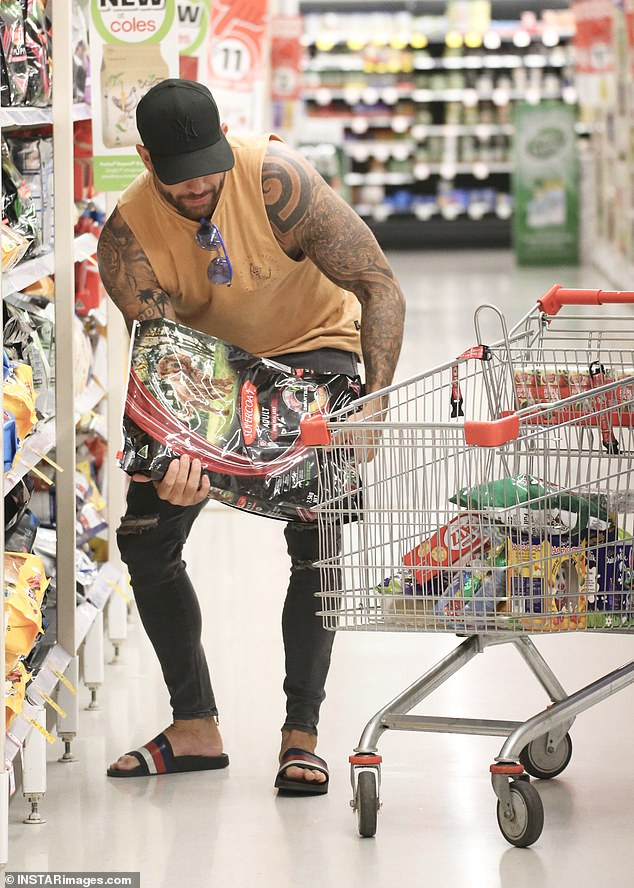 That's heavy! He then made his way over to the pet food section, lifting what appeared to be a heavy bag of dog food