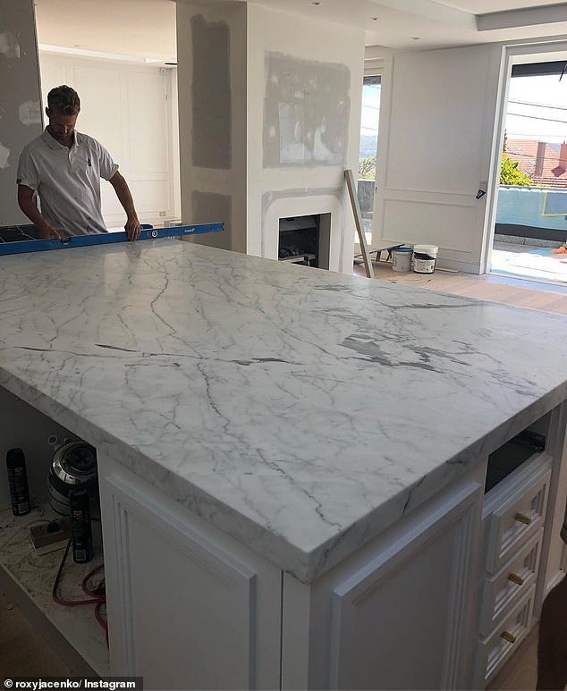 Finishing touches: The third picture shows a tradesman inspecting the marble bench top in place in Roxy's kitchen