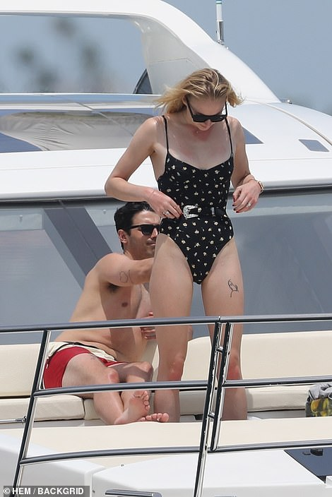 Lending a hand: Joe regularly re-applied SPF lotion to his fiancée's peachy        derrière