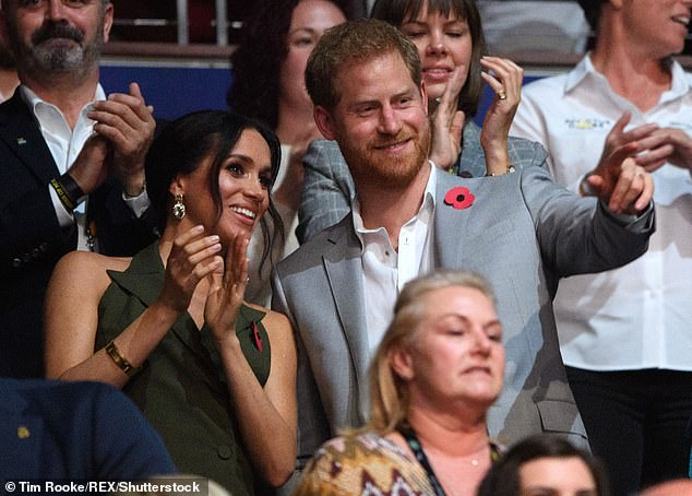 'Something I love about shooting the Sussexes is how affectionate they are with each other,' Tim said (Prince Harry and Meghan Markle at the Closing Ceremony in Sydney in 2018)