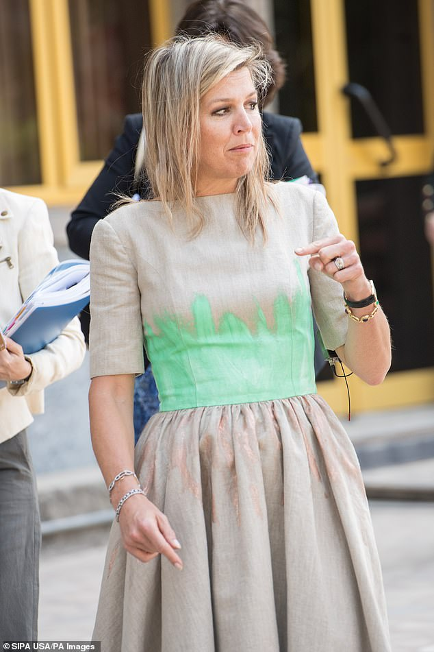 Maxima stunned with her unusual dress fitted at the waist and splattered with green and rose gold paint (pictured)