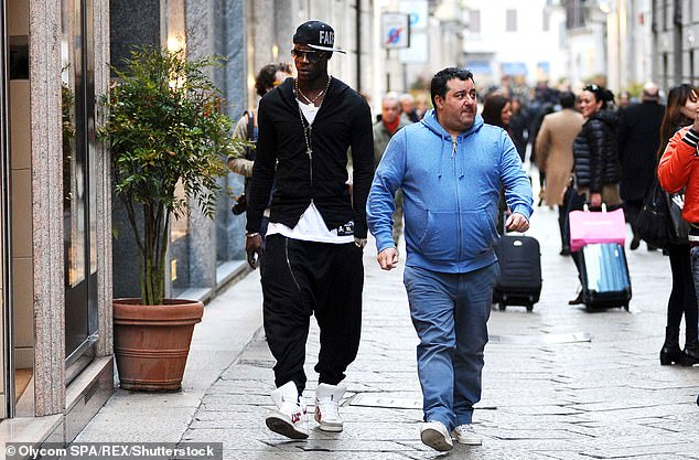 Raiola, pictured in 2013, walks with client Mario Balotelli (left) through Milan in Italy
