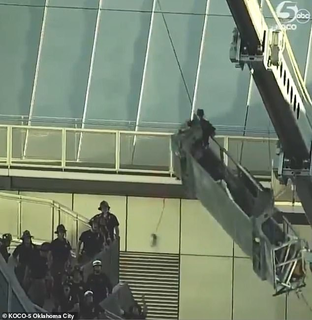Terrifying footage captured the basket as it swung out of control while firefighters tried to rescue the workers from the Devon Tower in Oklahoma City