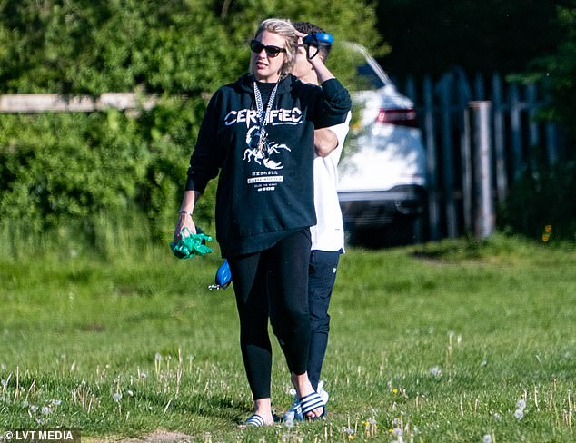 Sunny: The soap star slid her feet into a pair of Adidas sliders as she exercised her two beloved dogs during the sunny afternoon