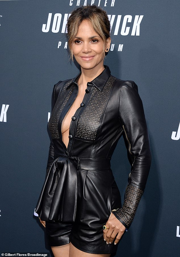 Halle's look:Berry was wearing a black leather romper which was unbuttoned to show off some cleavage, with a black belt around the waist and black stiletto heels
