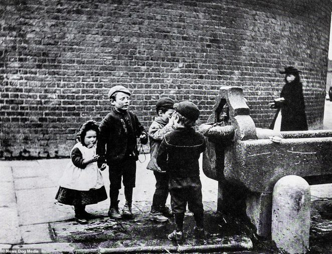 Filthy-looking children stand around a street fountain in Battersea, South West London, in the 1880s. This photograph is just one of a remarkable series of recently unearthed images which reveal the desperate lives of poor children in Victorian Britain