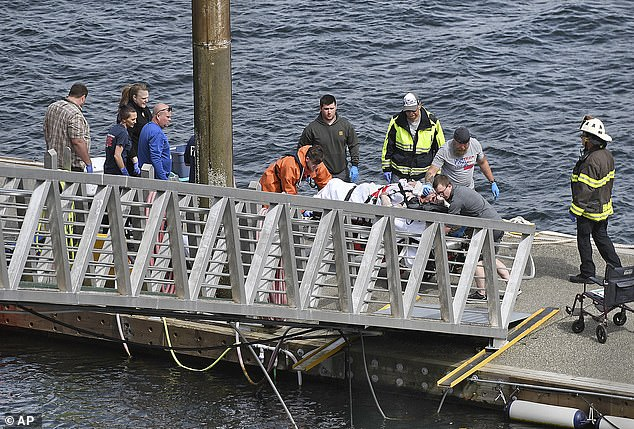 Emergency crews pictured above transporting an injured passenger on Monday