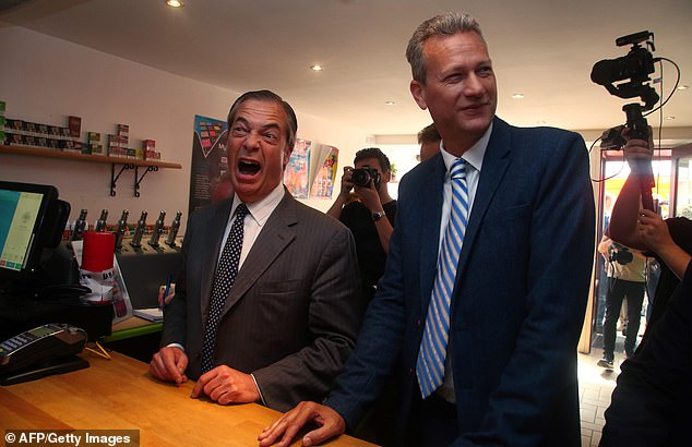 Nigel Farage (left) and a Brexit Party MEP candidate for Wales, Nathan Gill (right), react as they visit an e-cigarette and vape shop in South Wales yesterday