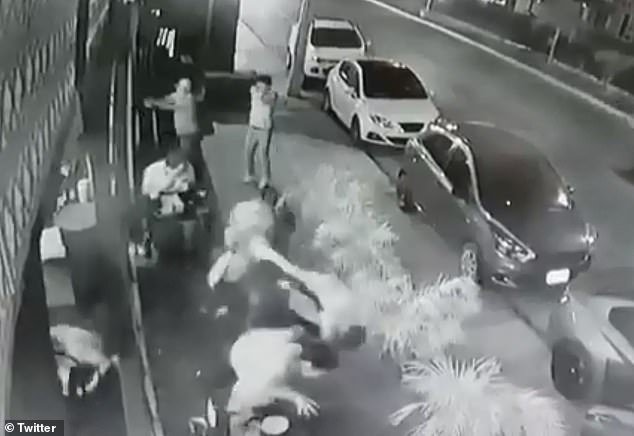 While one of the gunmen (top center left) points his weapon inside the restaurant, the other (top center right) aims it at the patrons sitting outside the eatery before firing