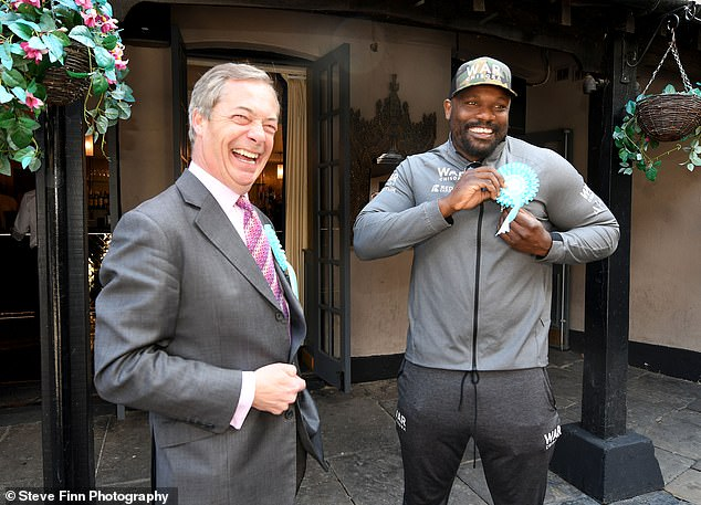 The Brexit Party leader laughs as boxer Derek Chisora pins on his rosette outside the Sugar Hut