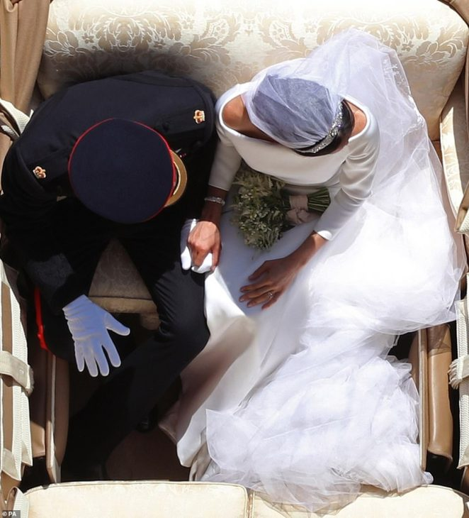 Prince Harry and Meghan Markle (pictured) ride in an Ascot Landau following their wedding at St George's Chapel in Windsor Castle in May last year. Both can be seen holding hands, in this, one of the most notable images from the British press over the past year