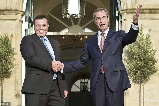 Millionaire Arron Banks (left) with current Brexit party leader Nigel Farage. Mr Banks has reportedly been funding Mr Farage's lavish lifestyle since 2016 -providing him with a £4.4m Chelsea home over the summer and a £32,000 Land Rover Discovery with close protection driver (pictured together in 2014 after Mr Banks donated £1 million to UKIP, Mr Farage's former party)