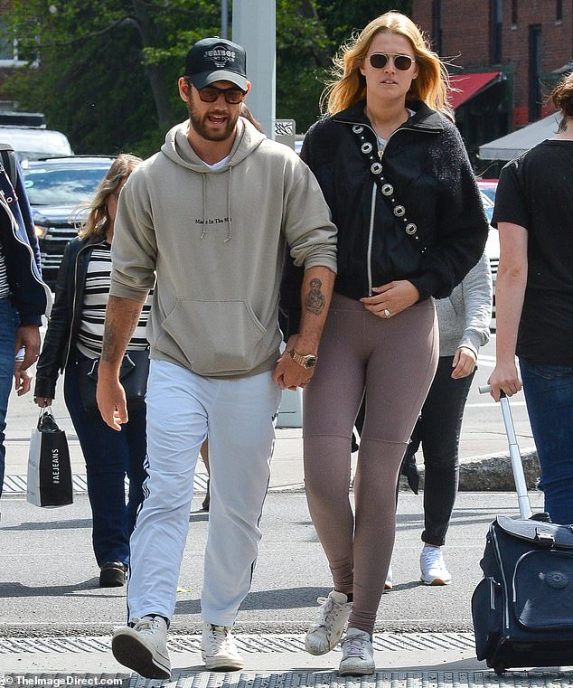 Spot the sparkle: Toni Garrn was wearing a ring on her wedding finger as she held hands with beau Alex Pettyfer in LA on Thursday