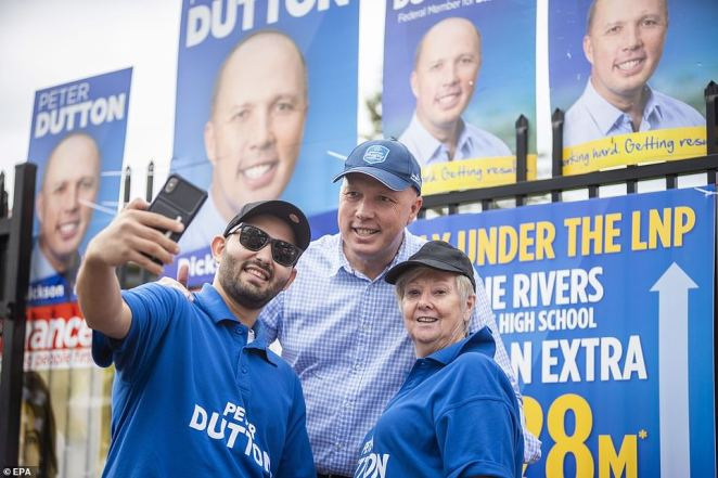 Australian Federal Member for Dickson Peter Dutton poses for a photo with supporters outside a voting station at Pine Rivers State High School on Election Day in Brisbane